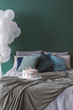Birthday cake with candles on cozy double bed with pillows and blanket, copy space on the empty green wall and bunch of white balloons in the corner