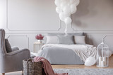 Bunch of white balloons above cozy double bed with grey bedding and white blanket, copy space on the empty wall and basket and armchair in the corner - 243452958