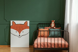 White poster with fox next to single metal bed with orange and dark green bedding - 243453172