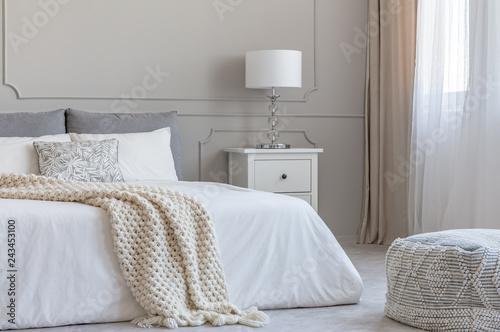 Beige woolen blanket on white duvet on king size bed in elegant bedroom interior