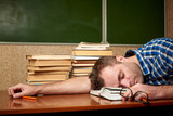 The exhausted young man sleeps on the open book. - 243457336