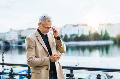 Mature businessman with smartphone standing by river in Prague city, using smartphone. - 243465956