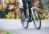 An unrecognizable man on electrobike cycling outdoors on a road in park. - 243466399