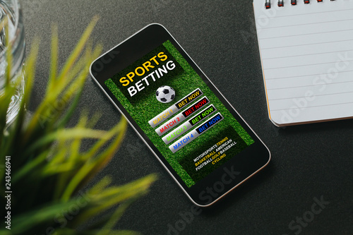 Sports betting website in a smartphone screen placed over a black desk.