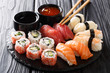 Leinwandbild Motiv Uramaki and nigiri sushi served in black plate closeup. horizontal