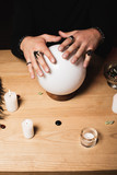 cropped view of esoteric with rings on hands above crystal ball near candles - 243471196