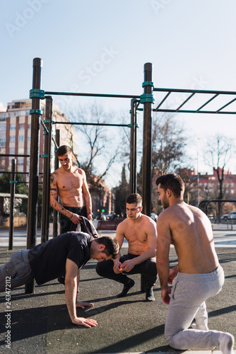 Poster Young athletic guys standing near man doing push up exercises in outdoor gym