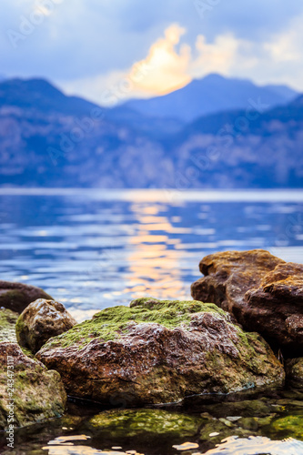 Colorful rocks in the water: Lago di garda at the evening, reflections on the water