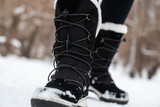 Black winter women's boots with white fur and white soles on the snow in the park - 243474701
