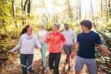 Small group of runners dressed in sportswear talking and walking through woods in autumn. - 243477784