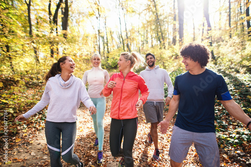 Poster Small group of runners dressed in sportswear talking and walking through woods in autumn.