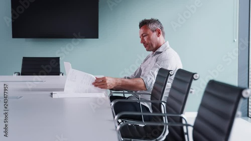 Poster Side View Of Casually Dressed Mature Businessman Working On Laptop At Boardroom Table In Meeting Room Shot In Slow Motion