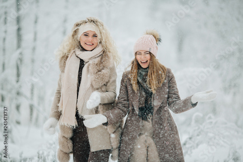Photo of two blondes throwing snow on walk in winter forest