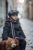 Two children, boy brothers, carrying suitcase and dog toy, travel in the city alone - 243485733