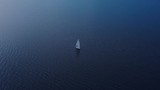 A lone boat floats aloft gorgeous blue water. - 243487330