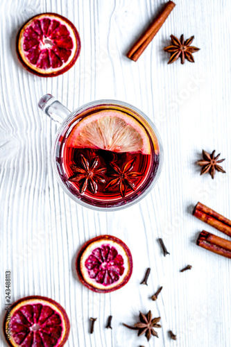 mulled wine with spices in cup wooden background top view