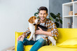 handsome smiling man sitting on sofa with beagle dog