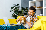 happy young man with laptop petting cute dog on sofa - 243491131