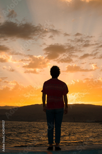Man standing firm looking at the horizon at sunset. - 243491137