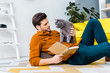 handsome man with book and lying on floor with cute grey cat