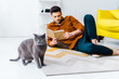 handsome man reading book and lying on floor with british shorthair cat