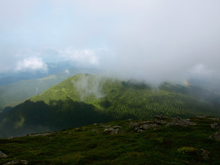 Picturesque landscape of Carpathian mountains with rainbow over them.  Heaven kitchen prepares rainy whether in summer in mountains. Eastern Carpathians, Ukraine