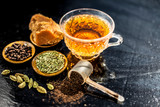 Close up of popular type of tea on wooden surface earlier dunked a lot i.e. Jaggery tea with ingredients like fennel,jaggery or gud,black pepper,tea leaves, milk, and green cardamom. - 243501942