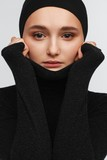 Portrait of a beautiful teenager girl in a black golf sweater and hat