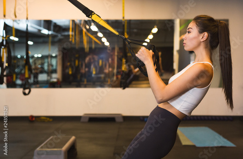 Sportive woman exercising with trx gym equipment