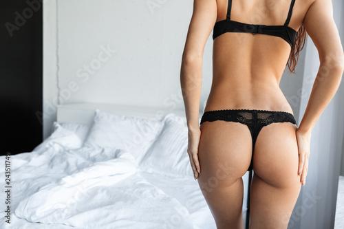 Leinwandbild Motiv Brunette woman wearing lingerie posing in bedroom.
