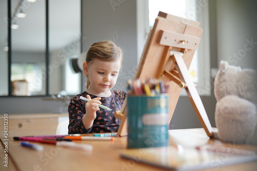 Leinwandbild Motiv Young girl drawing by herself on easel at home