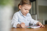 Young child playing by herself on tablet at home - 243512536