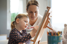 "Постер, картина, фотообои ""Mother and young daughter drawing together at home on easel"""