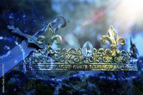 mysterious and magical photo of silver king crown and sword over the stone covered with moss in the England woods or field landscape with light flare. Medieval period concept. - 243513767