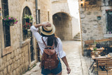 woman walking by tight streets of kotor - 243515310