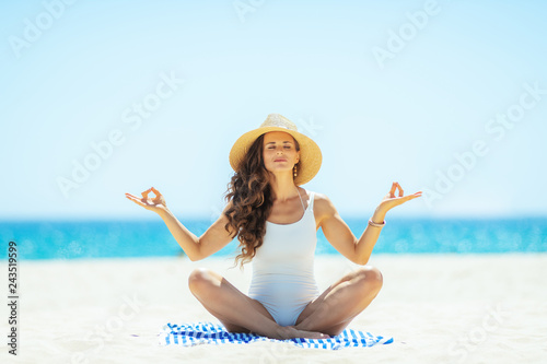 Wall mural woman doing yoga while sitting on striped towel on seashore