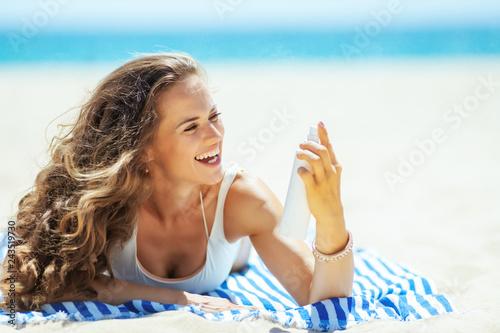 Leinwandbild Motiv happy woman applying SPF while laying on striped towel