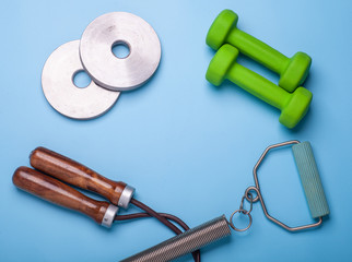 dumbbells, jumping rope and expander isolated on blue background, fitness concept, top view © Schum