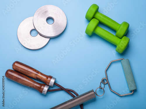 dumbbells, jumping rope and expander isolated on blue background, fitness concept, top view