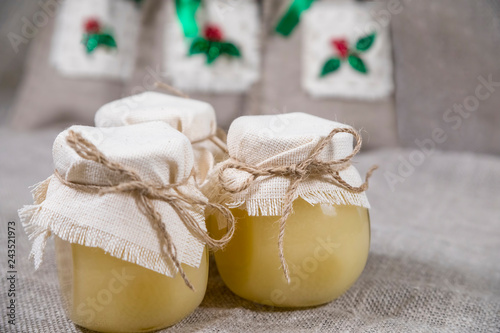 Three glass jars full of honey covered with cloth with handmade sacks of herbal tea on a linen fabric.