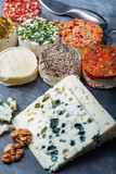 Assortment of French fresh white soft goat cheeses with different tastes topping made with herbs, paprika, indian curry, bruscetta, chives and dried tomatoes and piece of blue cheese Roquefort