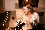 Portrait of an excited cute girl in casual clothes holding unopened present box by the fireplace - 243525319