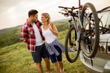 Loving couple stnding next to the car with bicycles - 243527526
