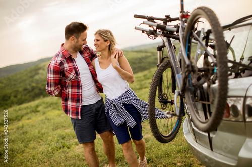 Leinwandbild Motiv Loving couple stnding next to the car with bicycles