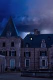 Old castle with illuminated window at dusk. - 243528727
