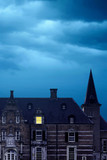 Old castle with illuminated window at dusk. - 243528728