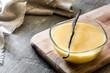 Bowl of homemade vanilla custard on wooden table