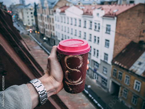 Wall mural man hand holding hot craft cup of coffee or tea in daylight with view to blurred city background. Enjoy, lifestyle, take away breakfast concept