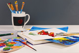 Hobby ,Painting, Art, Creativity concept. Artistic equipment : brushes, tubes of paint, palette and paintings on the table - 243538964