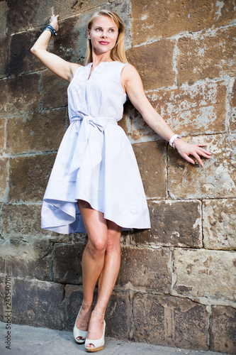 female standing near the stone wall - 243540701